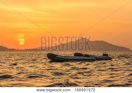 Boats against the rising over the island the Tyrant sun.