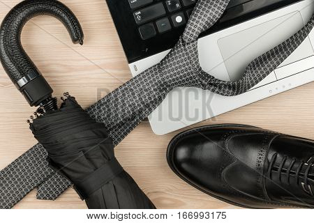 Classic mens black shoes notebook tie umbrella lies on desk. View from above