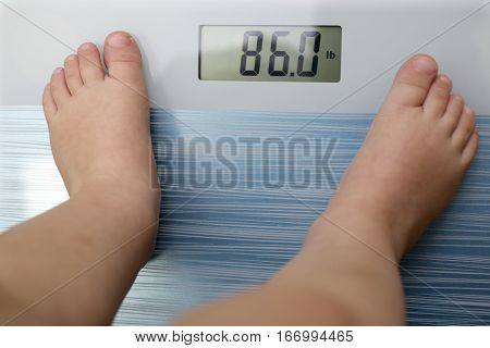 Children overweight young boy on a bathroom scale