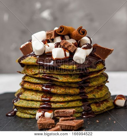 Non-traditional green sweet pancakes with chocolate and marshmallows. Love for a healthy desserts concept.
