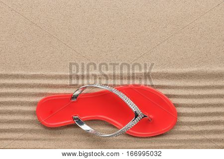 Trendy red flip flops decorated with rhinestones standing on the beach sand. View from above