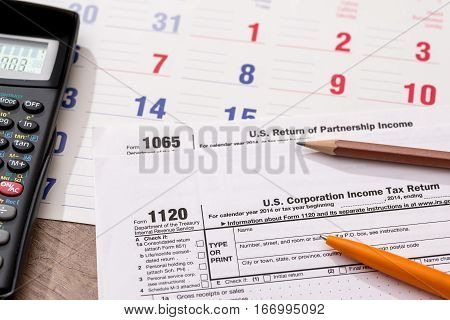 Form 1120 Corporate Tax Return with Calendar Calculator and Pen