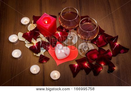 Candles, red rose petals, heart shaped gift box and two wine gases - Romantic Valentines Day Concept.