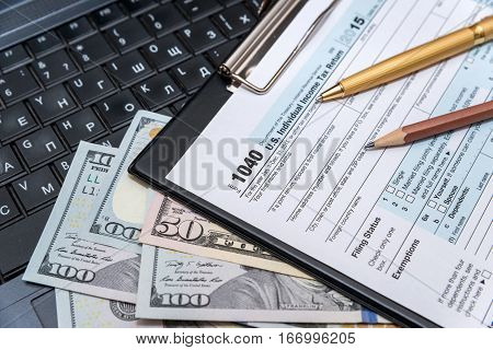 tax form 1040 with laptop. close up