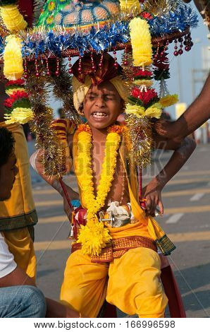 Kuala Lumpur Malaysia - 20 January 2011: A young boy devotee struggles with carrying the ceremonial kavadi during Thaipusam. During the Hindu festival devotees carry kavadis as part of a thanksgiving or supplication ritual.