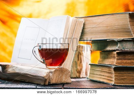 Cup of tea on rustic wood board. Stack of old books near teacup. Open book behind it.
