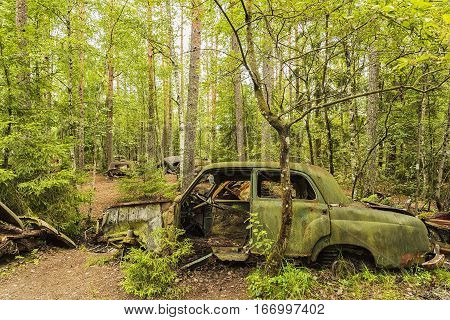 KIRKOE MOSSE SWEDEN - 28 JULY 2016: A car graveyard situated in a forest at Kirkoe Mosse Sweden.