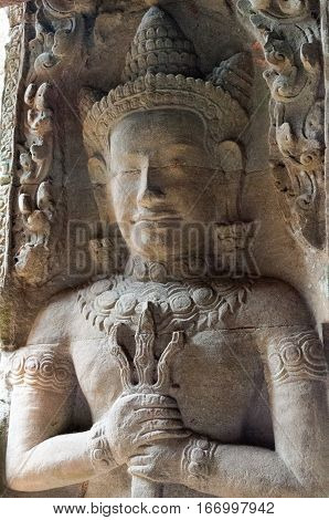 A carving of a dvarapala or guardian beside a doorway depcited with a mace in his hands
