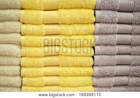Yellow towels stack. Shower towels in yellow and brown. Terrycloth towels in pile for selling. Home decor cloth in department store. Terry towels vertical pile on shelf. Home textile photo background