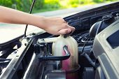 Asian girl's hand checking level of coolant car engine. poster