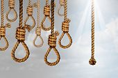 Despair and hope concept as a group of deadly hanging noose knots representing desperate suicidal psychological misery with one individual straight rope as a positive helpful liberation symbol. poster