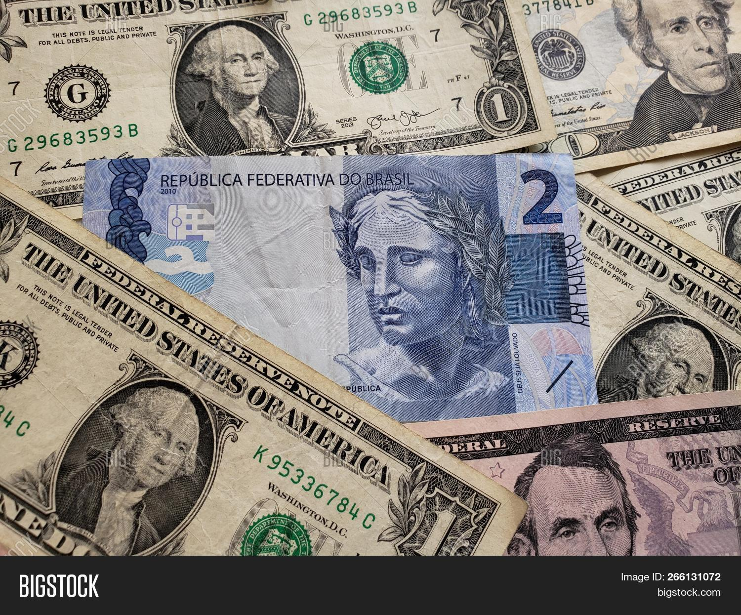 Brazilian Banknote Of Two Reais And American Dollars Bills Background Texture