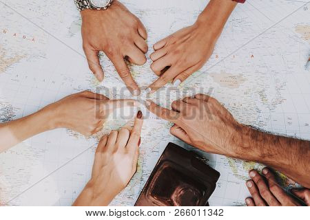 Group Of Young People Pointing On Place On Map. Closeup Of Travelers Planning Route Together By Usin