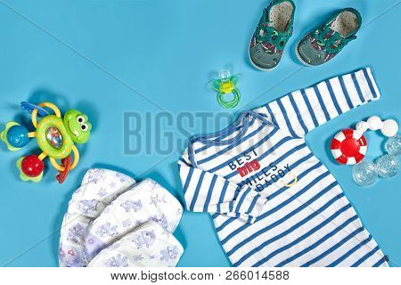 Baby clothing, toiletries, toys and health care accessories on blue background. poster