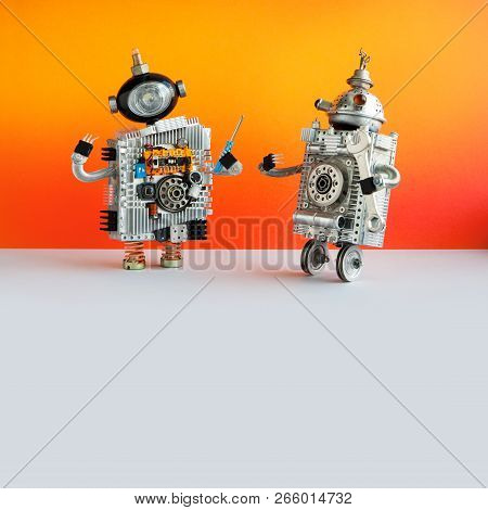 Two Repairman Robots With Screwdriver And Hand Wrench. Funny Technician Robotics Characters On Brigh