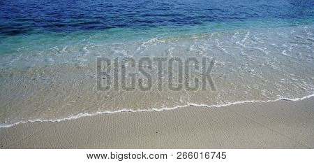 A Refreshing Ocean Blue Background With A Shoreline Breaking On Smooth White Sand.