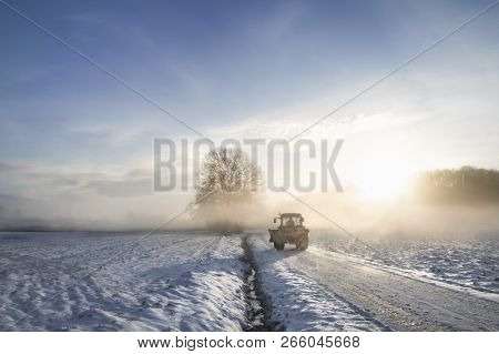 Tractor Silhouette On A Snowy Road, Crossing An Agricultural Field Covered In Snow, Through The Mist