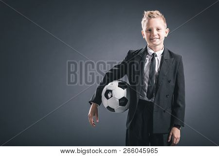 portrait of preteen boy dressed as businessman with soccer ball on grey background poster
