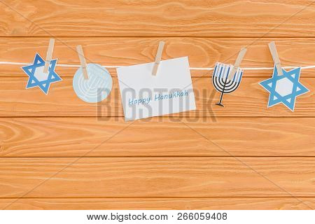 top view of happy hannukah card and holiday paper signs pegged on rope on wooden tabletop, hannukah concept poster
