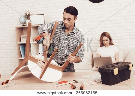 Assemble Furniture. Man Repairing Chair. Man Collects Chair. Furniture Assembler With Drill And Tool