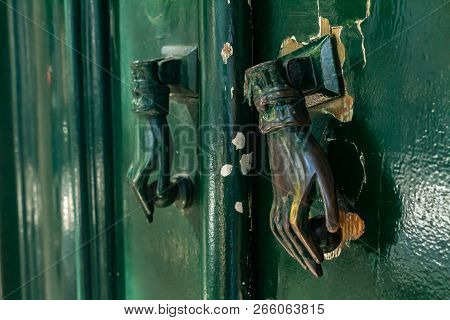 Hand-shaped Door Knocker On A Green Door. Ancient Artifact That Replaces The Timbre.