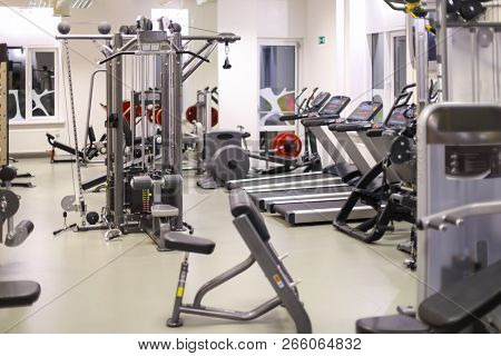 Modern empty gym hall with many different sport machines - treadmills, weight machines