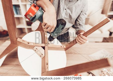Assemble Furniture. Man Repairing Chair. Man Collects Chair. Furniture Assembler With Drill. Woman O
