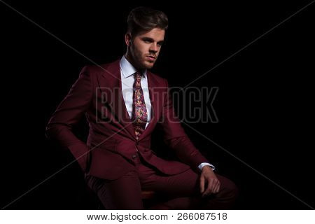relaxed young elegant man in burgundy suit is resting on a chair on black background