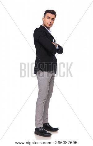 side view of confident businessman in black suit standing on white background, full length picture