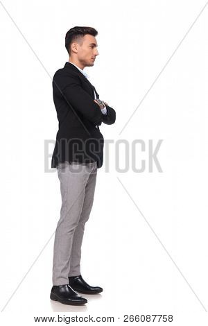 confident businessman with hands folded waiting in line while standing on white background, full length picture