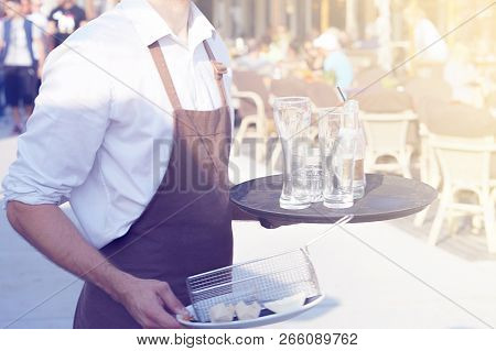 A Waiter Is Holding A Tray With Dirty Dishes And Leftover Food In A Cafe On The Beach. Waiter Cleani