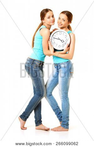 Two smiling women holding a clock. Twins, girls models are surprised. Concept about time, tardiness, punctuality.
