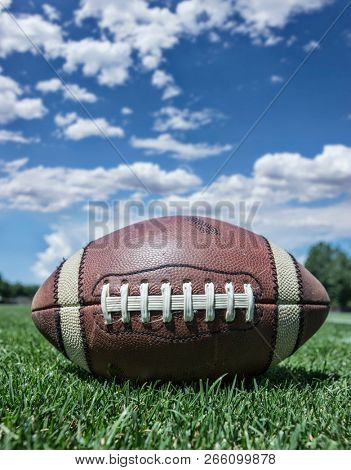 Closeup of a football sitting on grass football field outdoors Low angle view with blue sky in the background