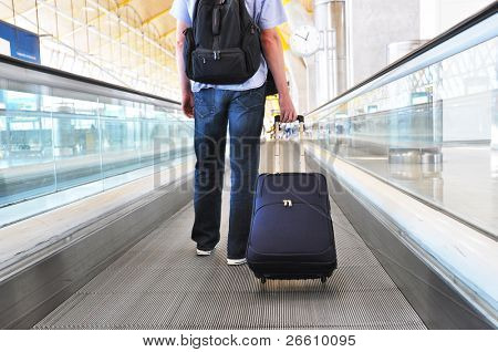 Traveler with a bag on the speedwalk