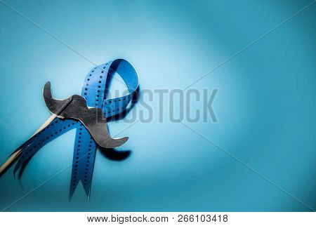 Blue Ribbon With Moustache On Blue Background. Prostate Cancer Awareness Month Concept