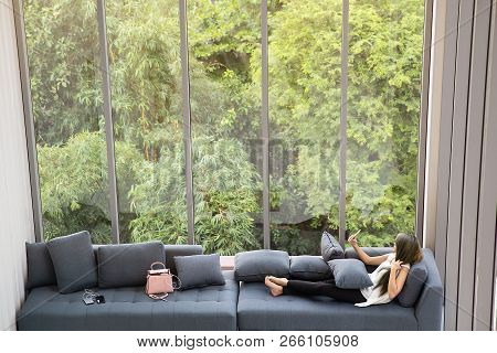 Asian Woman Laying On Sofa Near Big Glass Wondows, Relaxing Alone In House With Green Forest In Back