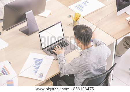 A Good-looking Business Man Is Sitting At The Desk, Analyzing The Information With  Computer At His