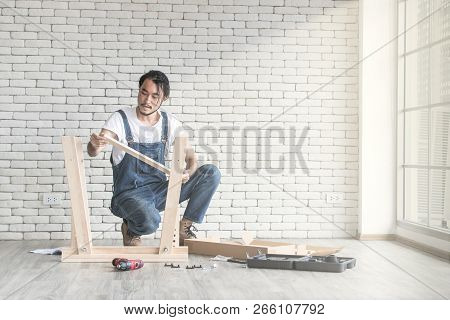 Young Man Working As Handyman, Assembling Wood Table With Equipments, Concept For Home Diy And Self