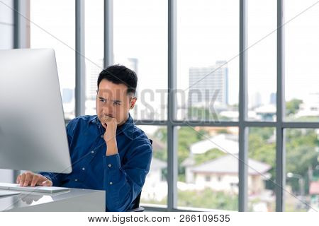 Young Asian Businessman Looking At The Computer Screen. His Face Expression Was Concerned With His W