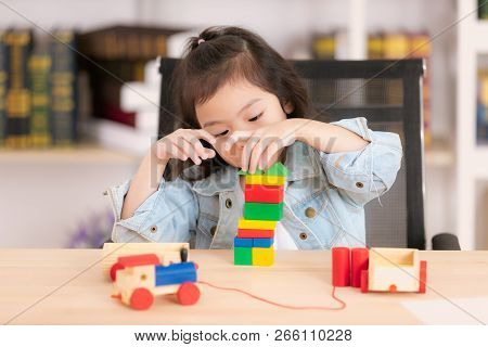 Lovely Cute Little Asian Girl In Jeans Shirt Playing Wood Block Toys On Desk. Concept For Funny Acti