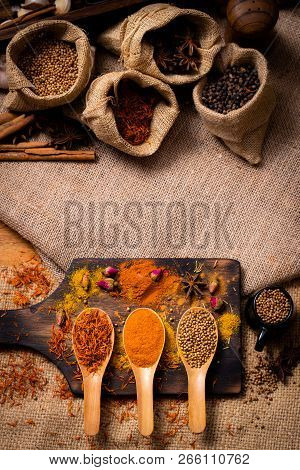 Colorful Various Spices And Herbs In Wood Spoon On Natural Texture Burned Wood Plate.