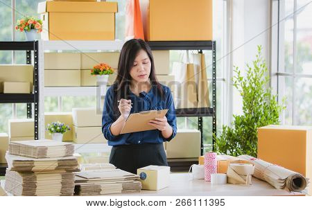 Young And Beautiful Asian Woman Standing Among Several Boxes And Checking Parcels, Working In The Ho