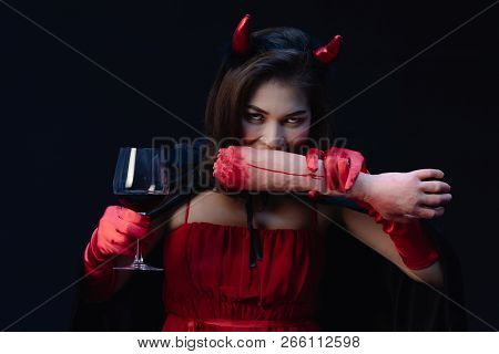 Studio Shot Of Beautiful Asian Woman In Red Cloth Like A Witch Or Devil Wearing Horn On Head, Holdin