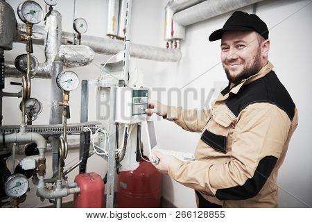 heating engineer or plumber inspector in boiler room taking readouts or adjusting meter poster