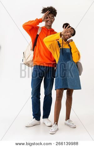 Full length photo of teen african american couple in colorful clothes smiling while showing ok sign isolated over white background