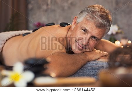 Portrait of senior man with hot stones on massage table looking at camera. Smiling mature man pampering himself at spa with body treatment. Man lying and relaxing during hot stone massage.