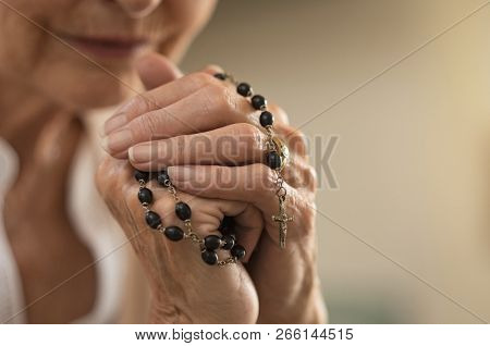Old wrinkled hands holding a rosary. Closeup of christian senior woman hands holding rosary beads and crucified cross while praying God. Mature catholic lady holding black rosary and praying.