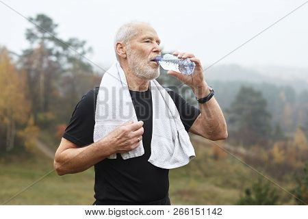 Portrait Of Tired Active Mature Sixty Year Old Man In Black T-shirt Drinking Water From Plastic Bott