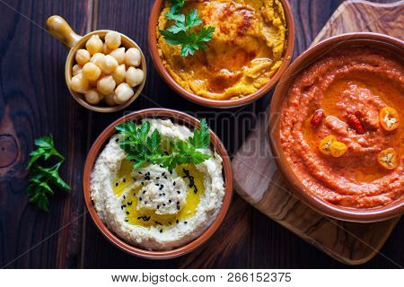 pumpkin hummus red pepper hummus and lentils hummus on wooden table