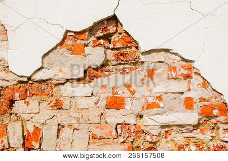 Stone texture background of weathered red brick stone wall, texture of stone red bricks with flaked stucco. Stone texture wall background